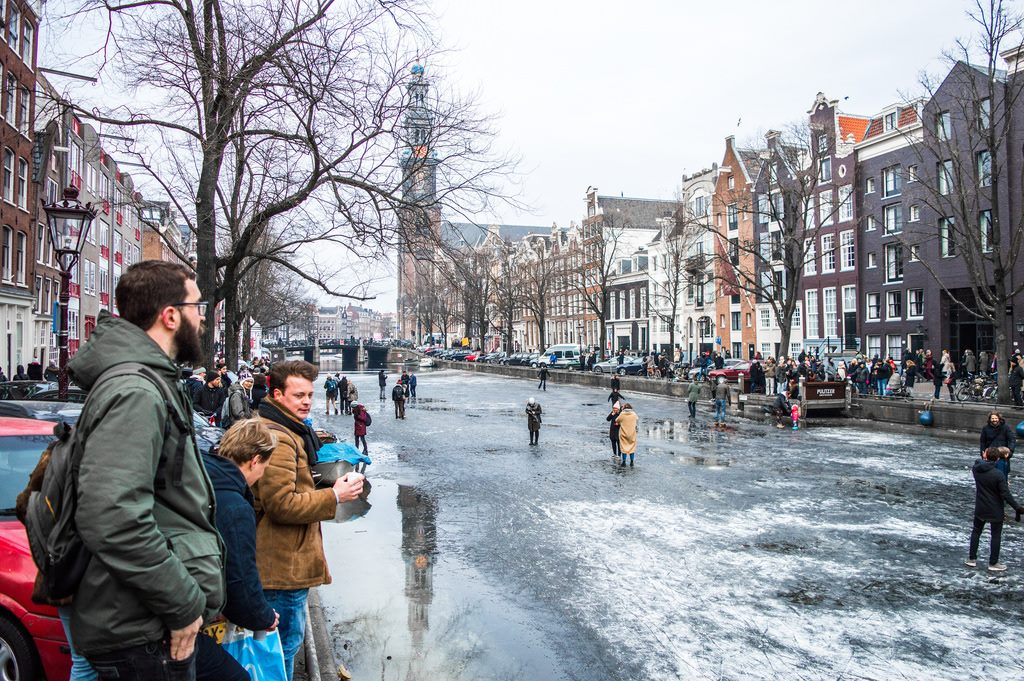 Bystanders watch the ice skaters on the frozen canal