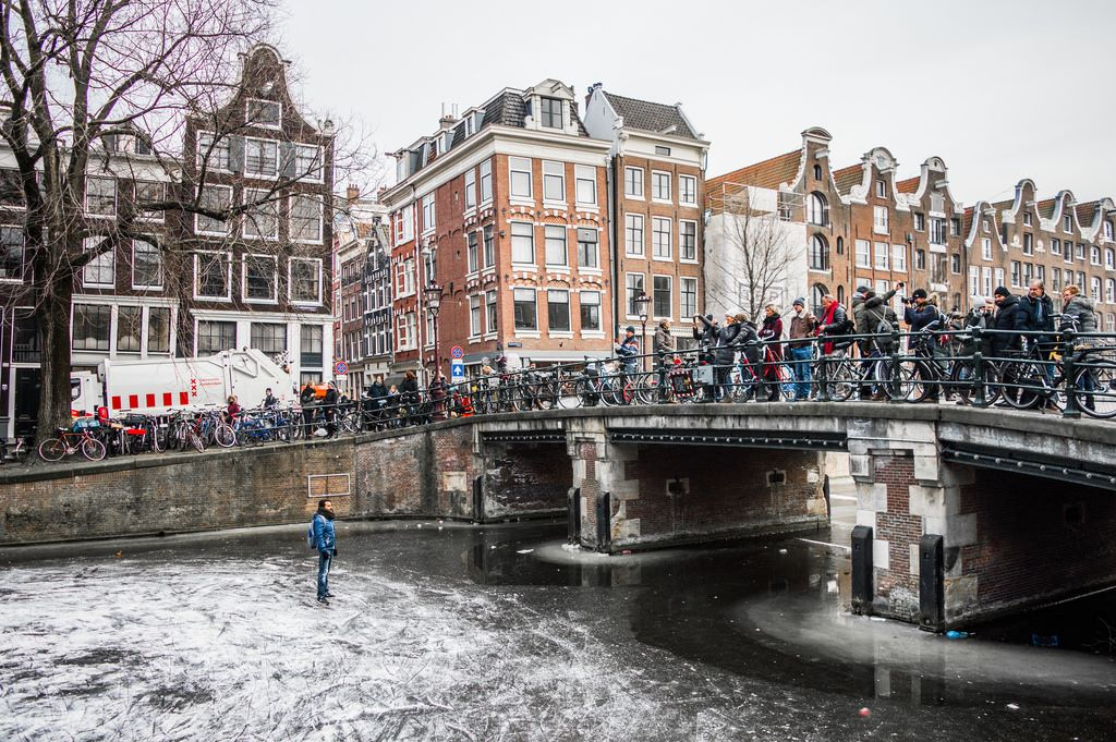 A bridge full of people above the frozen canals in Amsterdam