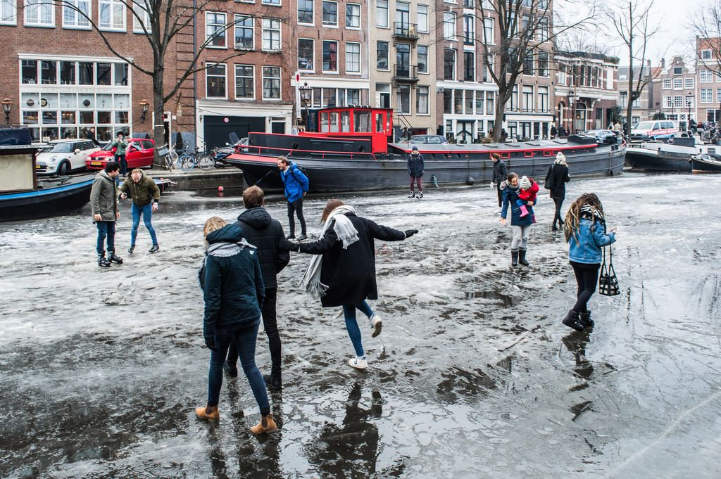 Several people stand on thin ice on the frozen canals in Amsterdam