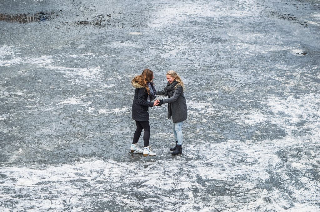 Two girls hold on to each other on the frozen Prinsengracht canal