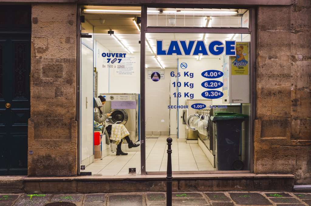 A frontal view of a self-service laundry, where a woman sits and waits for her load to finish.