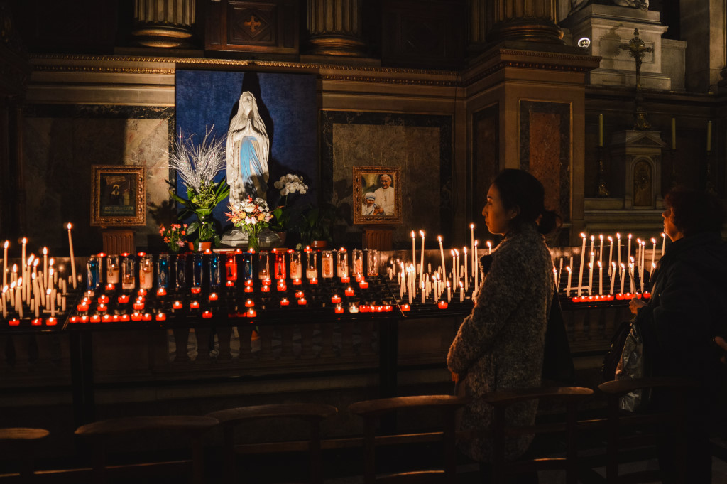 A woman observes the candle and a state of Mary at L'église de la Madeleine