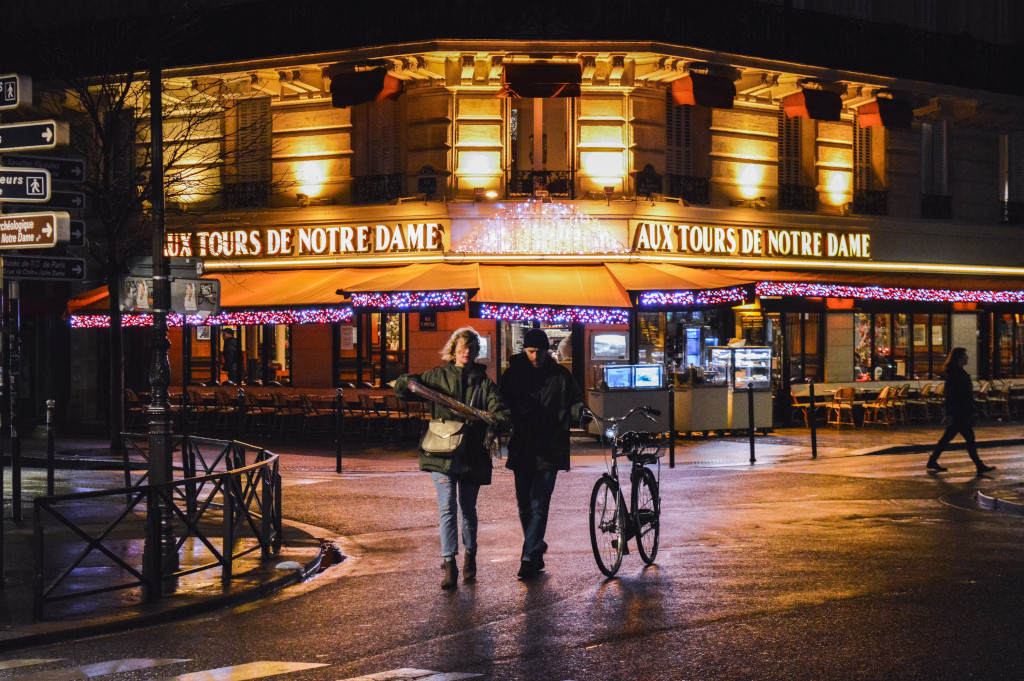 A couple walks the street during the night, past an illuminated café in the background