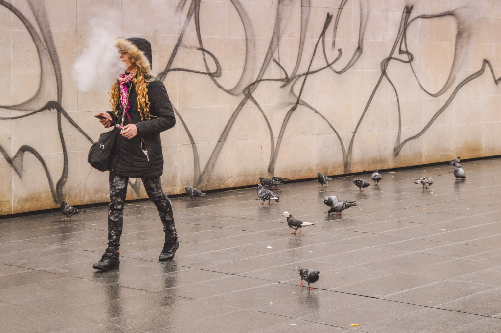 A woman smokes a cigarettes, exhales the fumes and walks past several pigeons