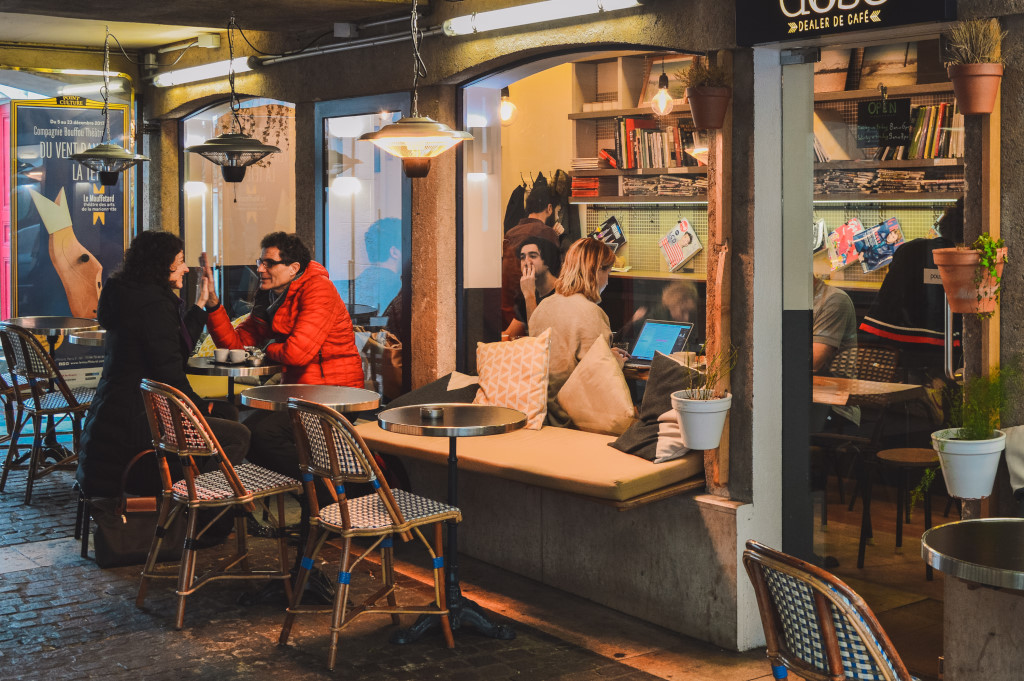 Parisians gather inside and outside of a café to have conversations and work on their laptops