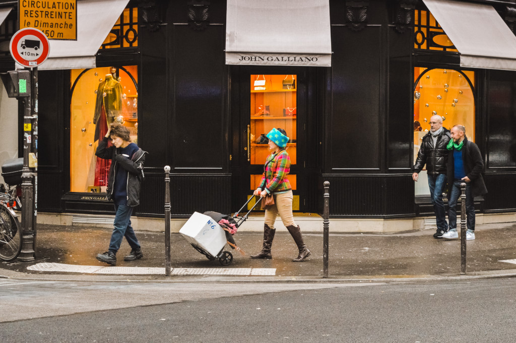 A woman dressed in several colourful prints pushes a package on a street in Paris.