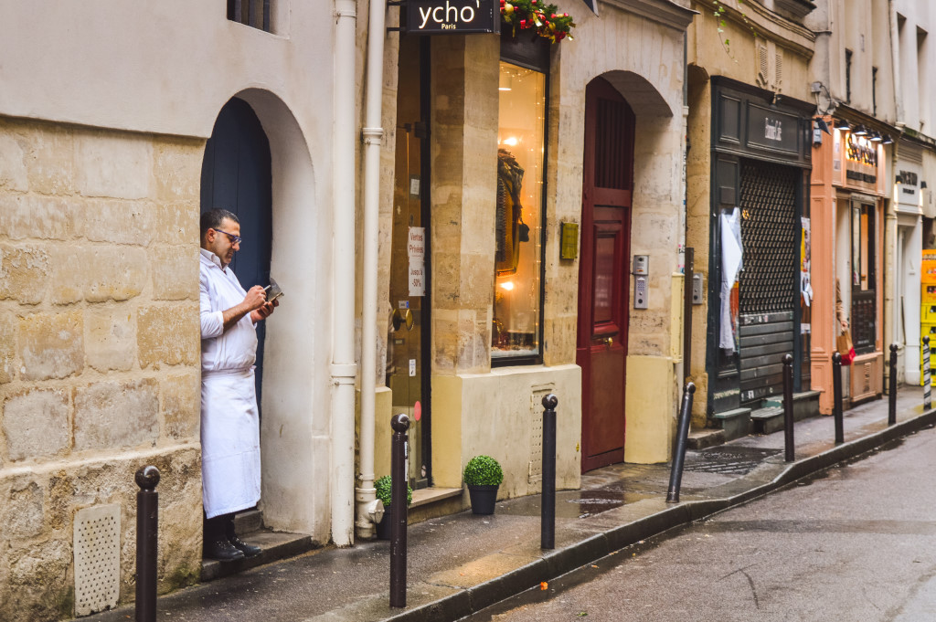A chef on his break looks at his phone and smokes a cigarette in a doorstep