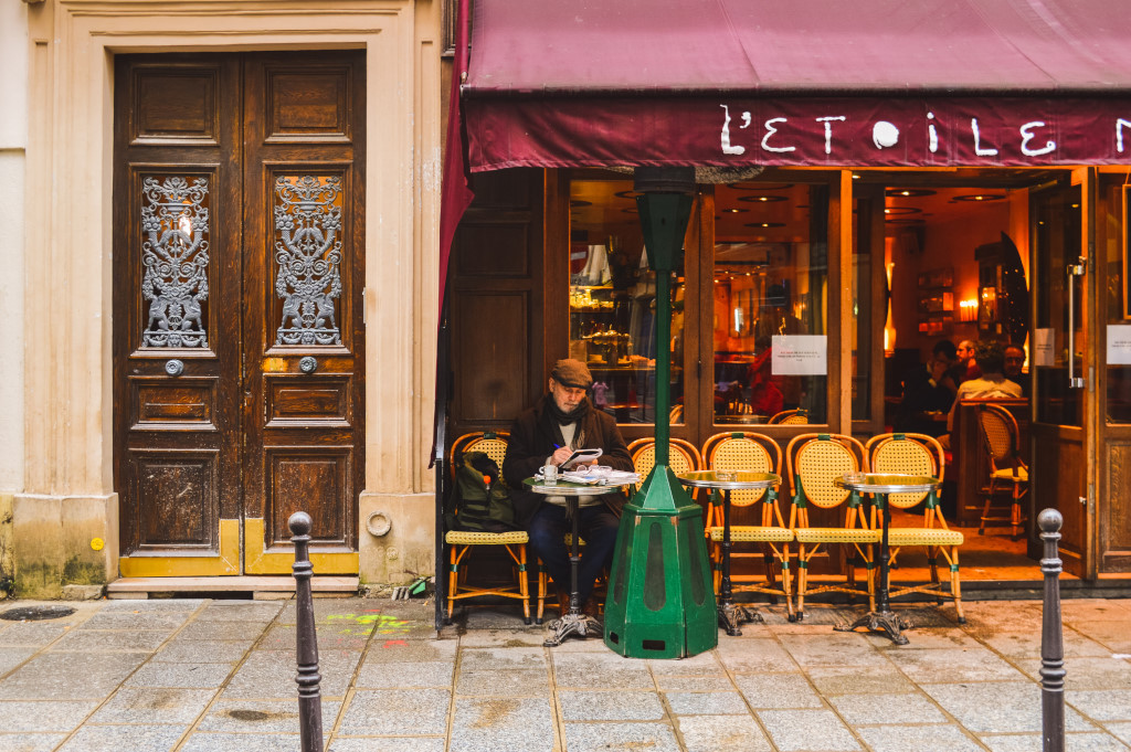 A solitary man writes in his notebook at a sidewalk café.