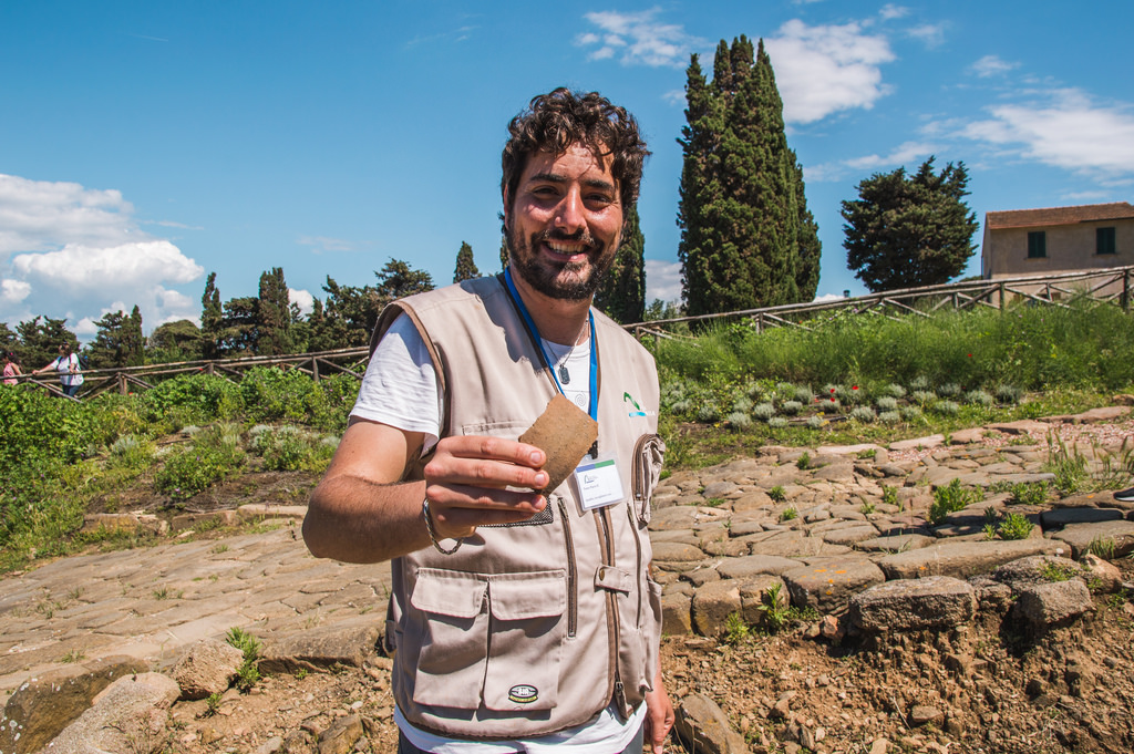 Flavio shows a piece of ancient pottery while smiling