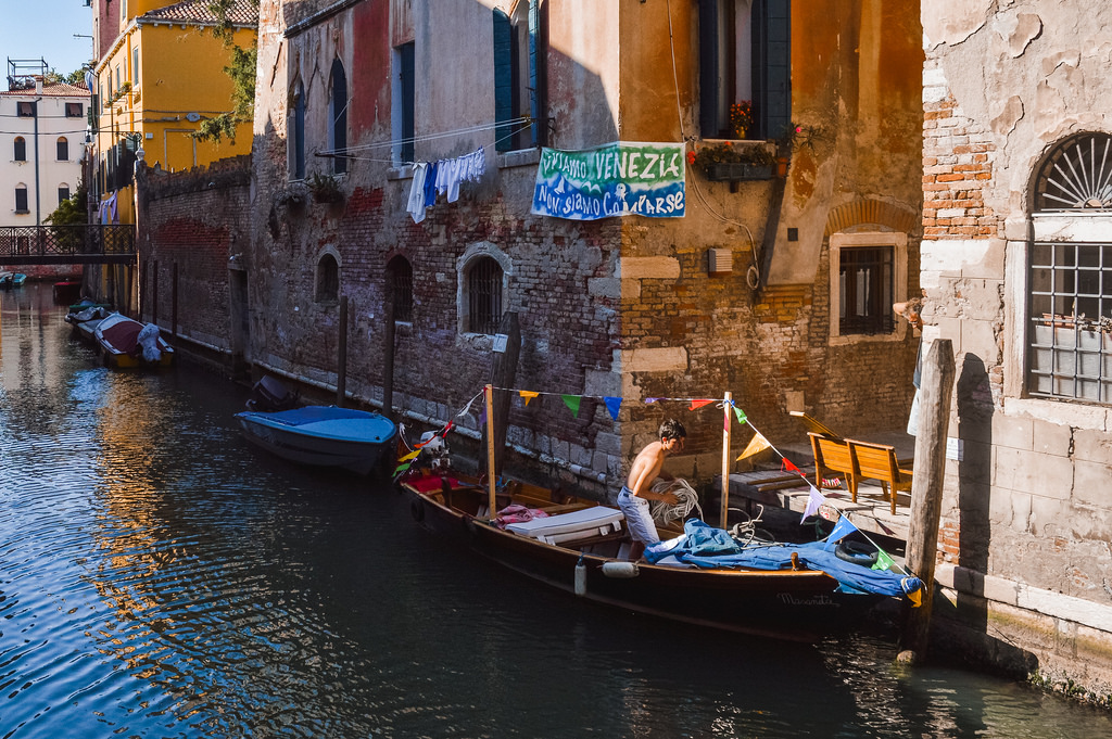 A young man in Venice decorates his boat for the Festa del Redentore