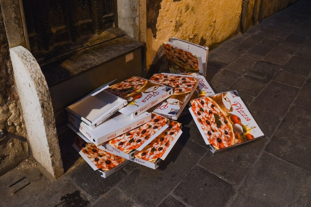 A pile of empty pizza boxes on the streets of Venice