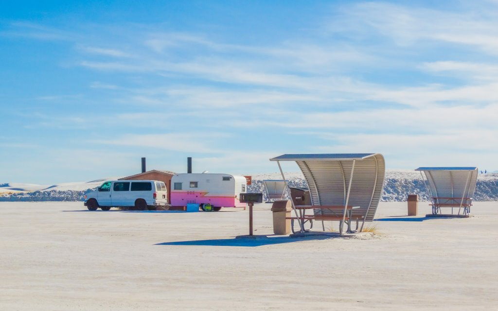 A car stop near White Sands National Park, including a white car with a white and pink trailer attached to it.