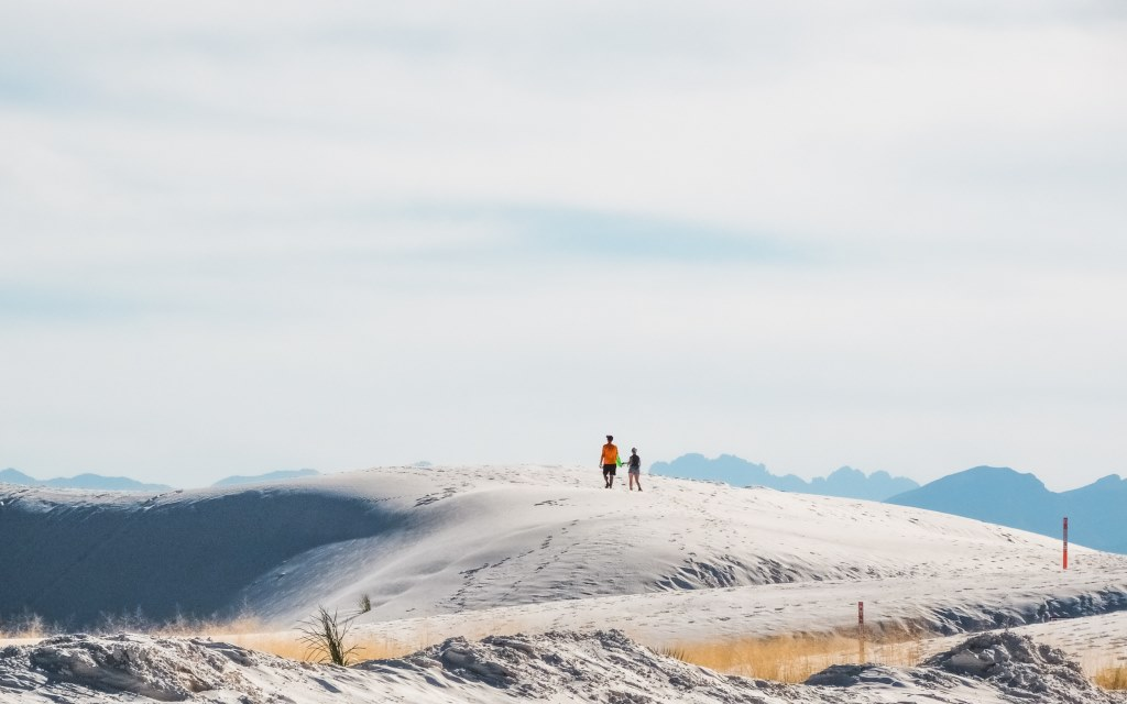 A couple walks across the sandy hills at White Sands National Park.