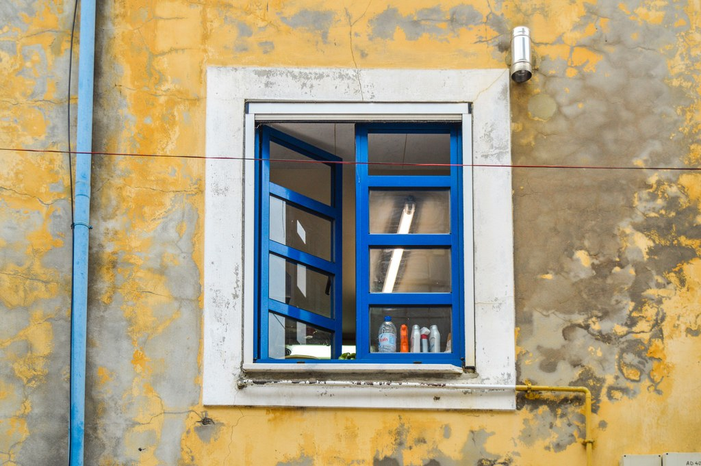 A yellow wall and blue window frame, both in a relatively unkempt state.