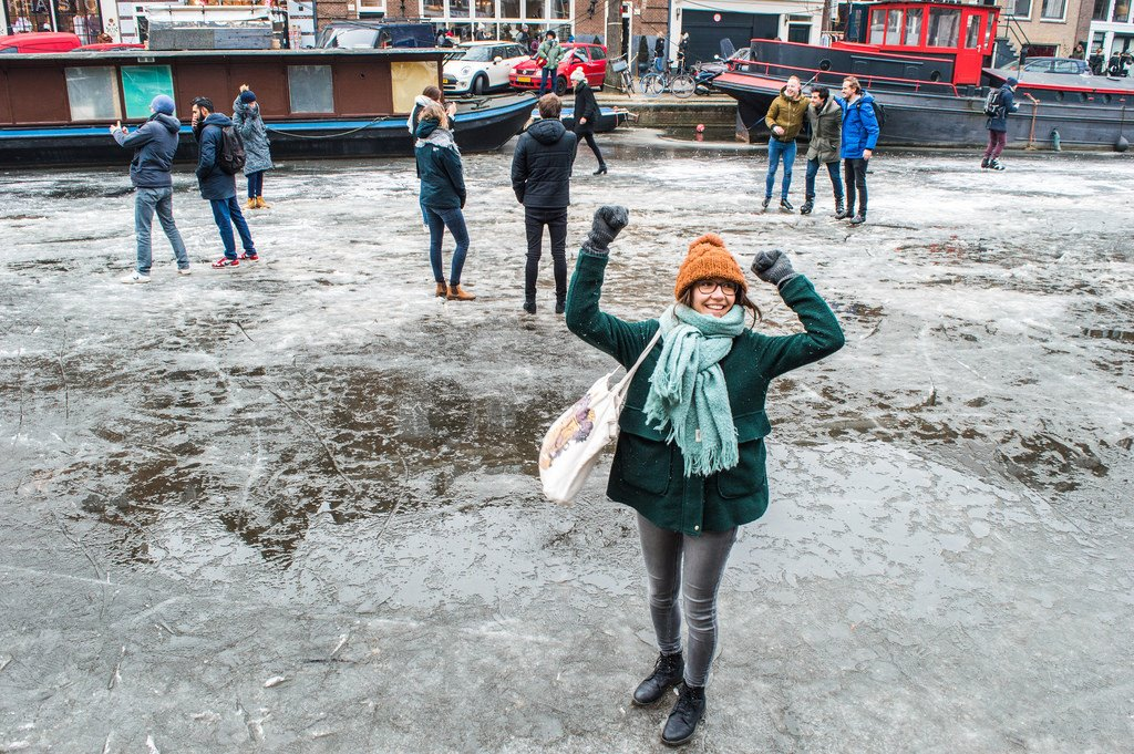 A girl pumps her arms in the air on a frozen canal in Amsterdam