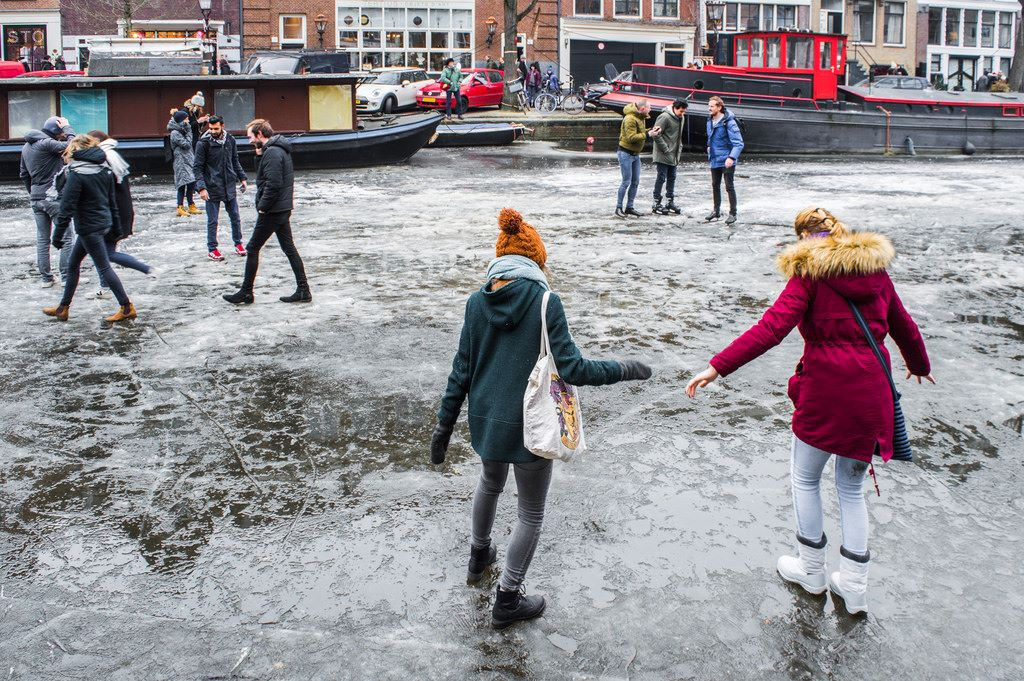 Tourists carefully tread the frozen canals in Amsterdam