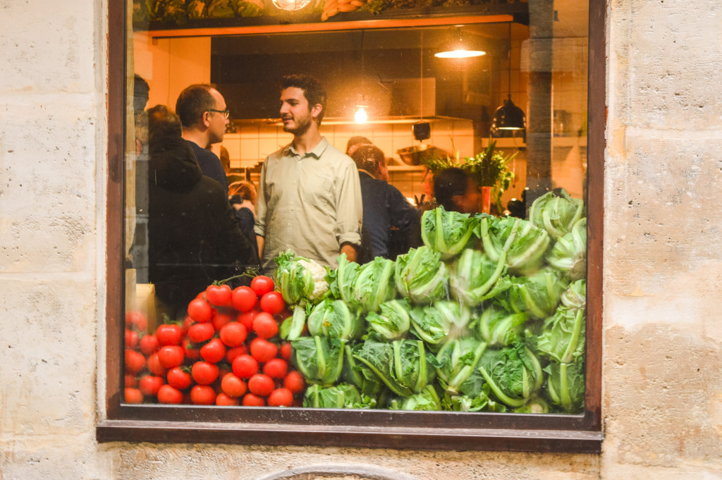 Photo of a restaurant in Le Marais, Paris. Tomatoes and lettuce are stacked in front of a window and two men inside are having a conversation.