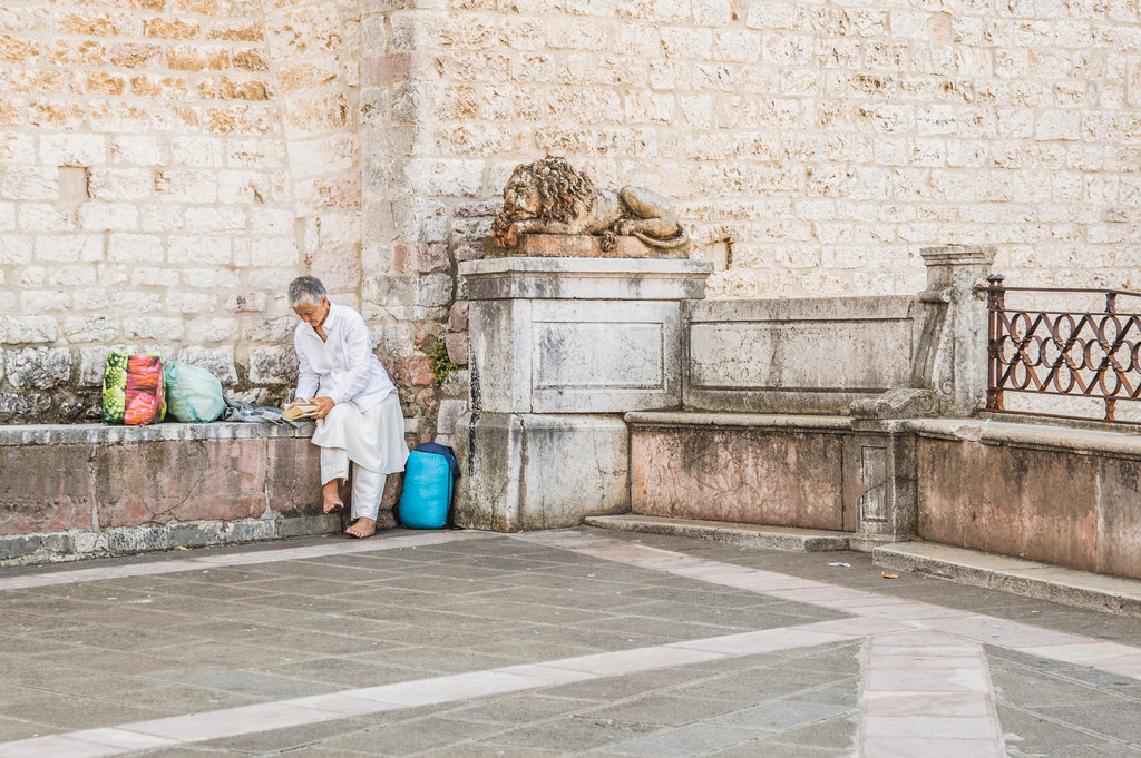 A female pilgrim in Assisi, dressed in white and without shoes.