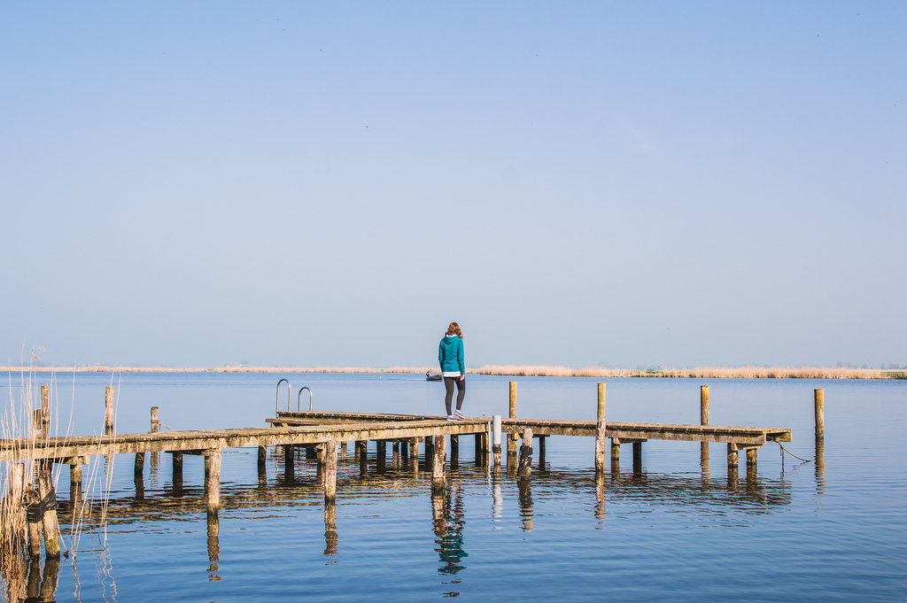 A girl walks on a wooden boardwalk that floats above a lake