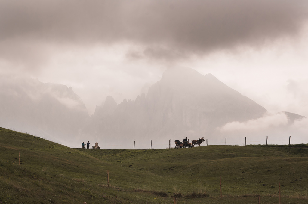 A cloudy day in the Dolomites, with silhouettes and a horse and carriage in the background.