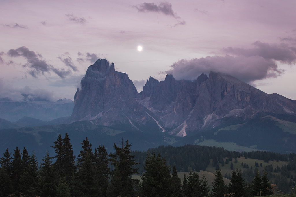 The moon rises above the Sassolungo mountain after an autumn sunset in Val Gardena.