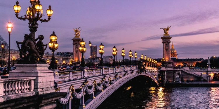 The sky above a historic bridge in Paris turns purple during the sunset.