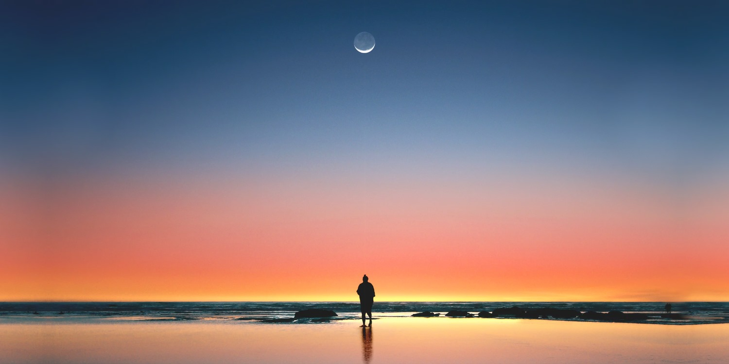 A silhouette of a person on beach, staring at the faraway moon.